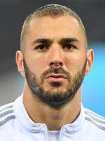 Twarz ogolonego na krótko Karima Benzemy w białym dresie z szarymi paskami na ramionach