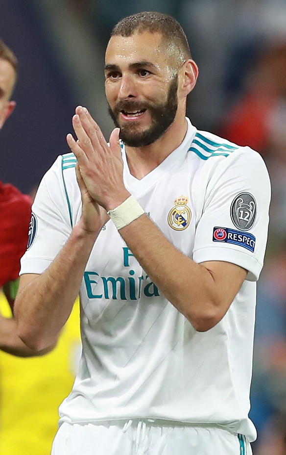 Karim Benzema w koszulce Realu Madryt na tle stadionu klaszcze w dłoń jakby przepraszał sędziego