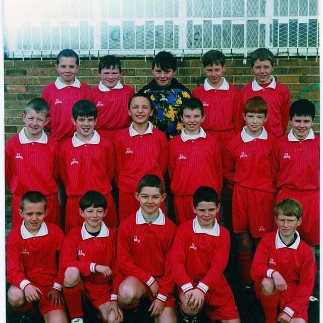 Dzieci Liverpool Schoolboys w czerwonych strojach piłkarskich ustawione w trzech rzędach