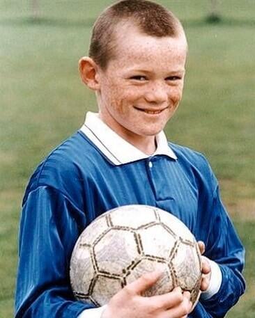 Młody Wayne Rooney w koszulce Evertonu uśmiecha się trzymając futbolówkę