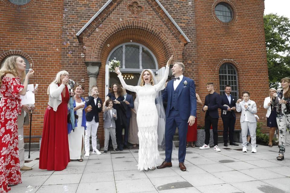 Laura von Lindholm i Peter Schmeichel w stroju ślubnym stoją otoczeni gośćmi przed wejściem murowanego kościoła