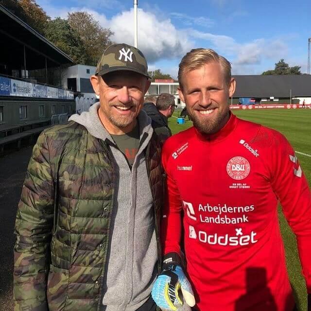 Peter Schmeichel w kurtce moro i Kasper Schmeichel w czerwonym stroju bramkarza pozują do zdjęcia na murawie boiska